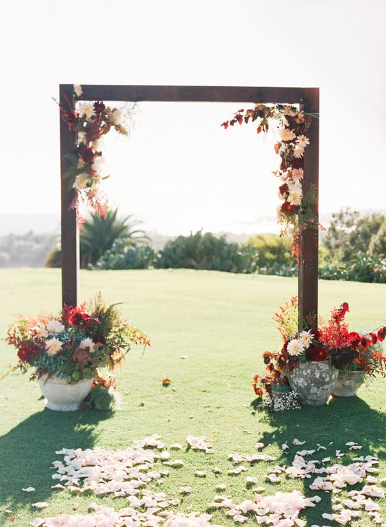 a bold rustic fall wedding arch decorated with burgundy and blush blooms, greenery and bold foliage, with matching arrangements in vases at the base