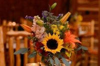 a bold wedding centerpiece of colorful lilies, sunflowers, roses and hydrangeas and candles around is a cool idea for a rustic wedding