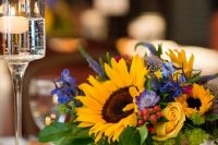 a bold wedding centerpiece with sunflowers, yellow roses, purple and blue flowers, astilbe and foliage is a fantastic idea