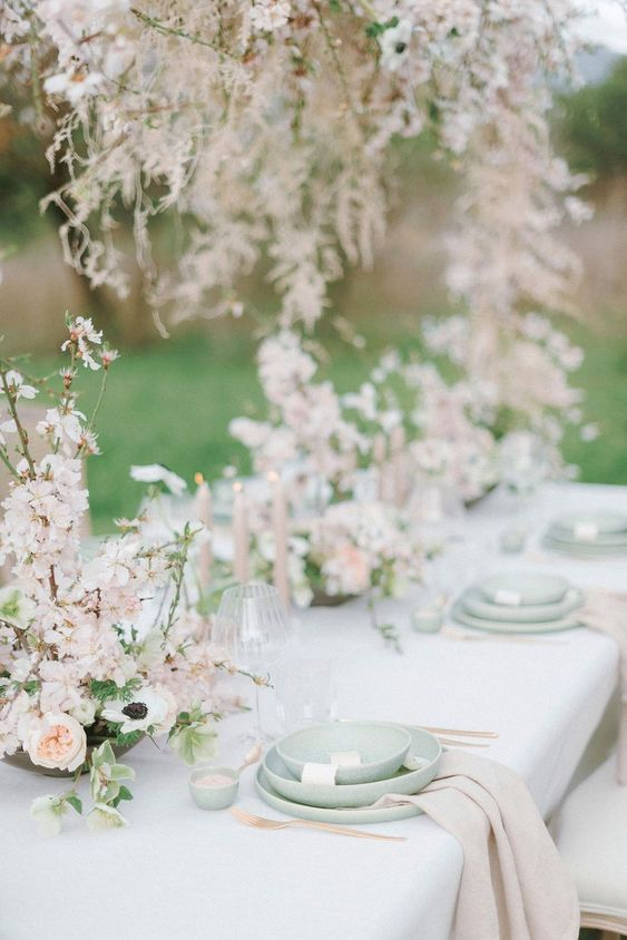 a breathtaking enchanted garden wedding tablescape done in pastel green and blush, with beautiful almond blossom centerpieces and green plates