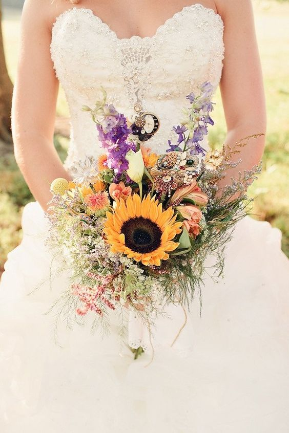 a bright and cool laid-back wedding bouquet with a single sunflower, billy balls, purple and orange blooms and lots of grasses for a more relaxed look