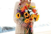 a bright and fun wedding bouquet with sunflowers, purple, red, orange and white blooms and greenery is a gorgeous idea for a boho bride