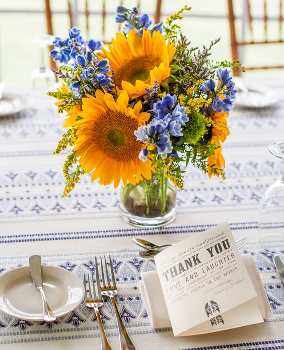 a bright and pretty summer wedding centerpiece of sunflowers and bold blue flowers, mimosas and some greenery is amazing for a colorful wedding