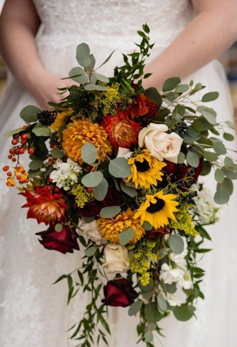 a bright cascading wedding bouquet of sunflowers, red and yellow dahlias, white and burgundy roses, greenery and berries