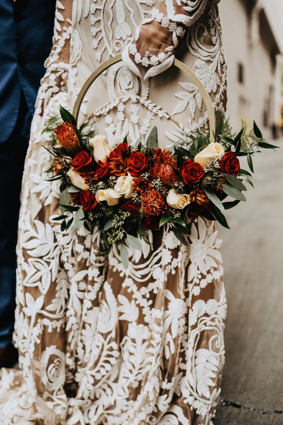 a bright fall boho hoop wedding bouquet with greenery, peachy and red blooms is a stylish idea for a boho wedding