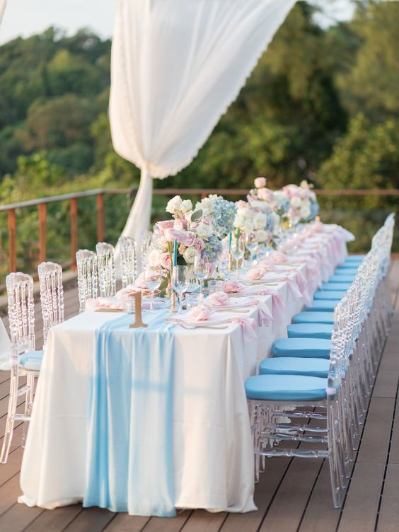 a bright glam wedding tablescape with a blue table runner and napkins, blue, pink and white blooms, blue candles and gold touches