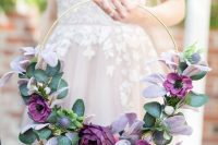 a bright hoop wedding bouquet of purple blooms, lilac and green foliage is a bold summer or fall idea