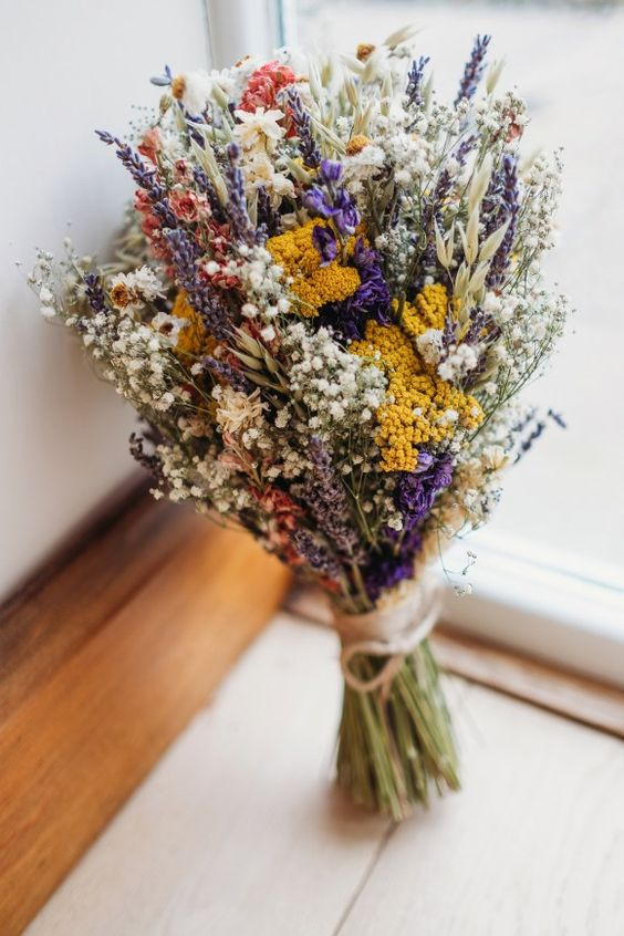 a bright summer wedding bouquet of baby's breath, lavender, bright yellow and red blooms is a cool idea for a boho or rustic bride