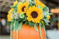 a bright summer wedding centerpiece of sunflowers, greenery and baby's breath placed into a pumpkin is perfect for a bold fall wedding