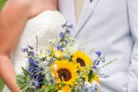a bright wedding bouquet with sunflowers, purple blooms, thistles and greenery is a cool idea for a summer wedding with a rustic feel
