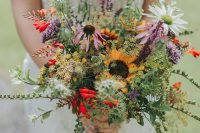 a bright wildflower wedding bouquet with greenery of various kinds, sunflowers, lilac and red touches and chamomiles is wow
