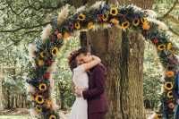 a cheerful rustic round wedding arch suitable for both a summer and a fall wedding, with pampas grass, greenery, sunflowers, blue and red blooms
