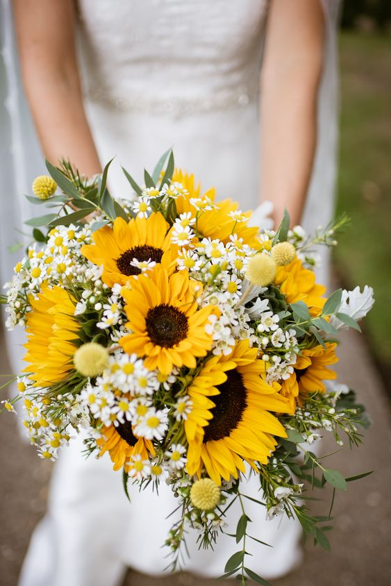 a chic and simple rustic wedding bouquet with sunflowers, billy balls, daisies and greenery is a lovely solution for a summer wedding