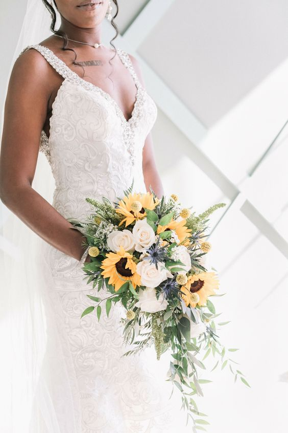 a chic cascading wedding bouquet of white roses, sunflowers, billy balls, greenery and thistles is a lovely idea for a summer bride