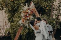 a chic fall boho wedding arch with yellow, pink, blush blooms, pampas grass and dried leaves is amazing