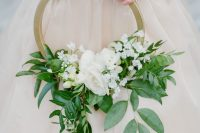 a chic gold hoop wedding bouquet with textural greenery and white blooms is a lovely idea for a spring or summer wedding
