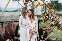 a chic hexagon wedding arch decorated with gilded branches and leaves, pink and peachy blooms, pink fronds and feathers