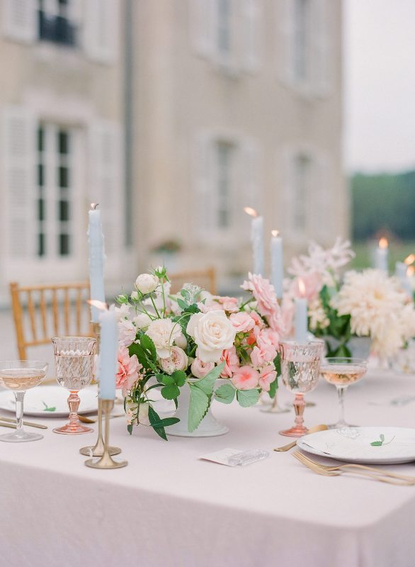 a chic pastel wedding tablescape with neutral and pink blooms and greenery, blue candles, pink glasses and a blush tablecloth