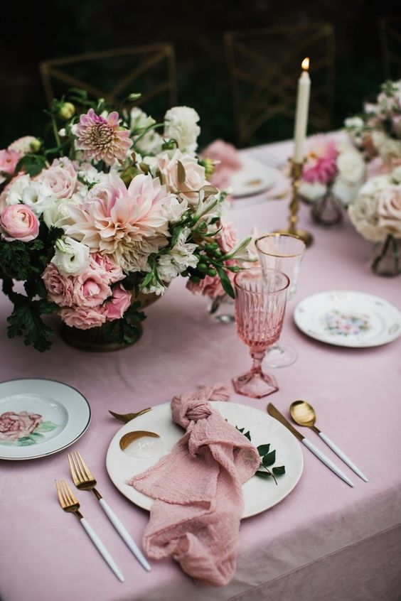 a chic secret garden wedding tablescape in rose, with beautiful and lush floral centerpieces, floral plates and pink glasses and linens