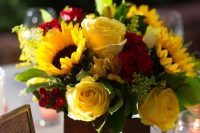 a classic wedding centerpiece of yellow and red roses, berries, sunflowers and greenery is a bold solution for a summer or fall wedding