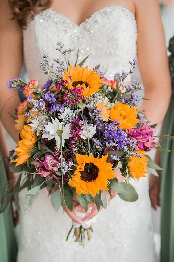 a colorful and lovely wedding bouquet of sunflowers, white, pink and purple blooms, greenery and grasses is amazing for a rustic bride