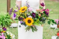 a colorful and sumptuous wedding bouquet with purple and deep purple blooms, fuchsia, pale pink touches, various greenery and sunflowers