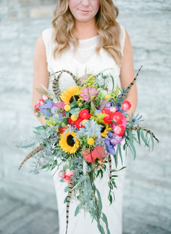 a colorful boho wedding bouquet with feathers, sunflowers, billy balls, greenery and red and purple blooms is cool for a boho bride