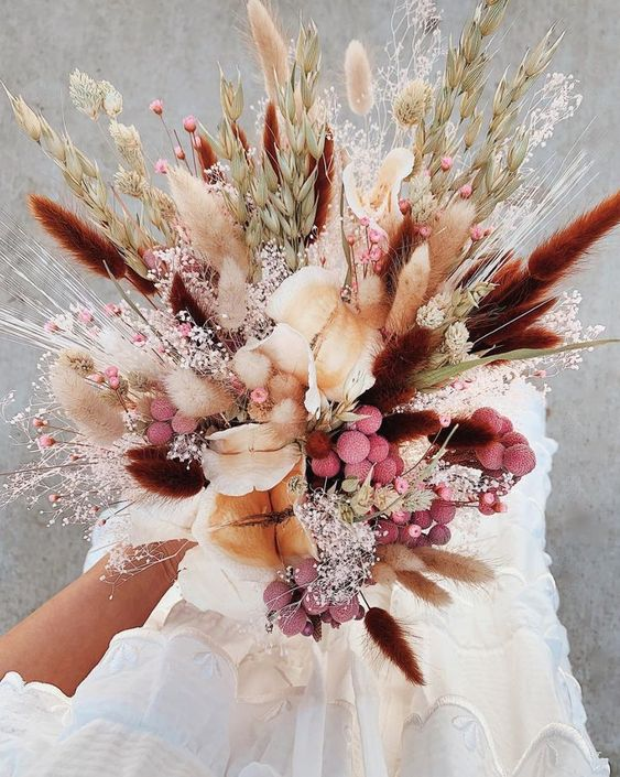 a colorful dried flower wedding bouquet with bright bunny tails, colorful billy balls, baby's breath, twigs and wheat is amazing for a summer or fall bride