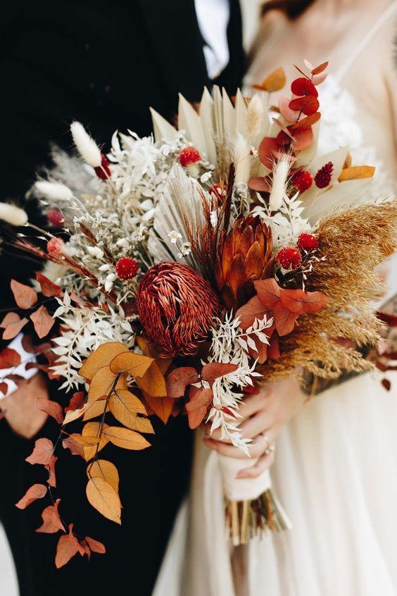a colorful fall wedding bouquet of bunny tails, bold dried foliage, a king protea, fronds, eucalyptus and wheat is a boho idea
