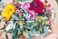 a colorful fall wedding bouquet with pink roses, burgundy dahlias, greenery, dried daisies and sunflowers plus euclayptus