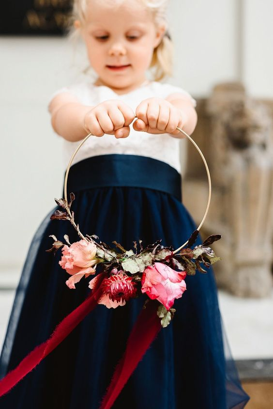 a colorful hoop wedding bouquet with greenery, pink and red blooms and long burgundy ribbons is a very cool and bold idea