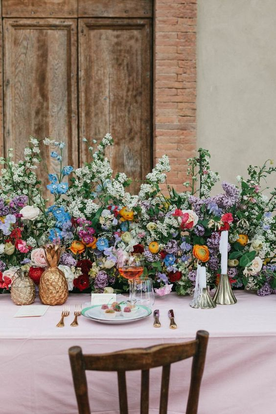 a colorful secret garden wedding table setting with a super lush greenery and bold floral table runner, brass candleholders and gold pineapples