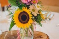 a colorful summer wedding centerpiece of sunflowers, pink and white blooms, greenery and lavender placed on a wood slice and with a wood slice table number