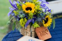 a colorful summer wedding centerpiece of sunflowers, thistles, astilbe and purple blooms plus eucalyptus covered with wine corks for a vineyard wedding