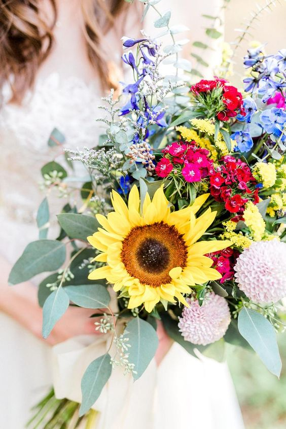 a colorful sunflower wedding bouquet with purple, blue, pink, red and blush blooms, greenery and large sunflowers is amazing for a summer bride