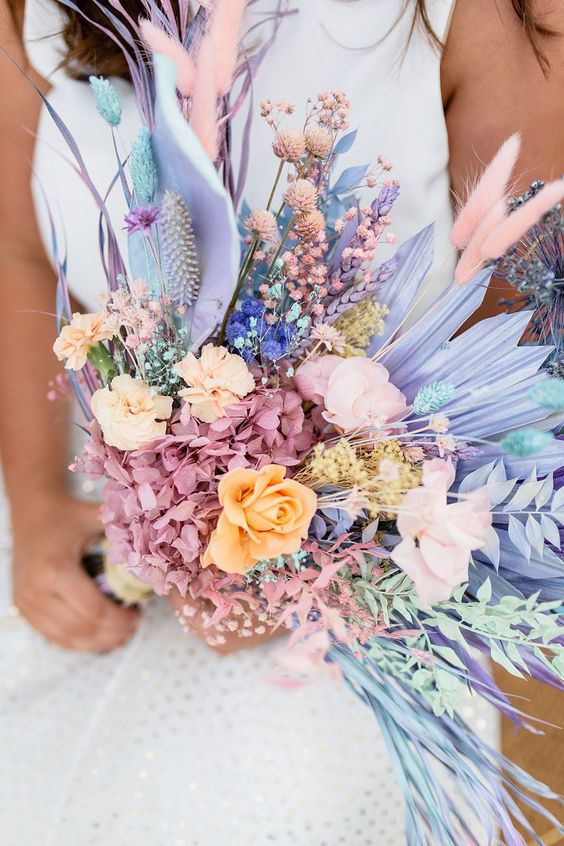 a colorful wedding bouquet with pink hydrangeas, peachy and pink roses, lilac fronds, pink bunny tails and blue grasses looks out of this world