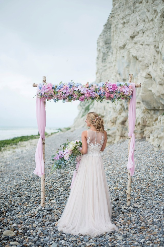 a cool beach wedding arch with pink, blue and lilac blooms, some greenery, pink fabric and a gorgeous sea view is amazing