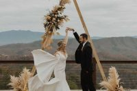 a cool fall boho wedding arch with pampas grass, dried foliage and blusha nd mustard blooms, candle lanterns and a lovely view