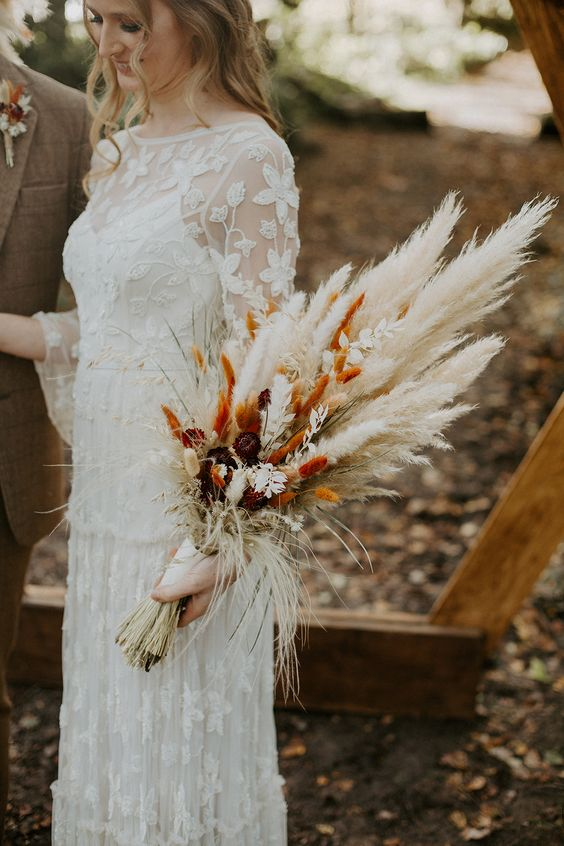 a cool fall wedding bouquet of dried bunny tails, pampas grass, blooms and grasses, neutral or spray painted for a fall boho bride
