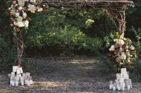 a cool rustic wedding arch of branches, twigs, white, green, pink, deep purple blooms, greenery and lots of candles at the base