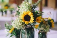 a cute rustic wedding centerpiece with sunflowers