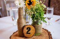 a cool rustic wedding centerpiece of sunflowers, daisies, gerberas, burlap and rope plus a wood slice is a lovely solution for summer