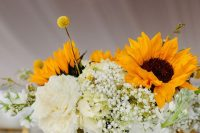 a cool wedding centerpiece with white roses, sunflowers, baby's breath and billy balls is a lovely and cute arrangement for a rustic wedding
