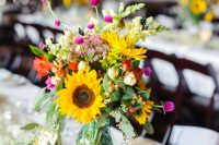 a cute and colorful rustic wedding centerpiece of a jar with sunflowers, red, pink blooms, greenery and berries plus baby's breath around is cool