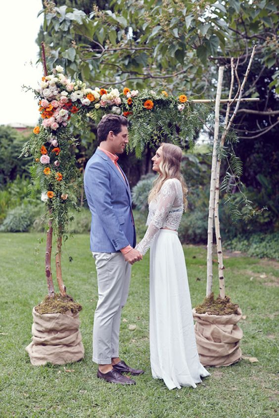 a cute rustic fall wedding arch of branches, pink, blusha nd orange blooms, greenery and moss in buckets wrapped with burlap