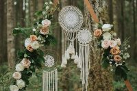 a delicate boho fall wedding arch with white, blush and rust blooms, greenery, dream catchers and foliage is amazing