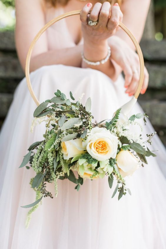 a delicate spring hoop wedding bouquet with greenery and white and peachy roses is a chic solution for a spring or summer wedding