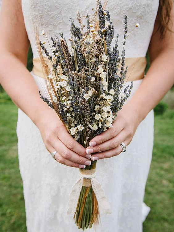 a delicate summer dried flower wedding bouquet of daisies, lavender and some grasses is a cool idea for a rustic or boho bride