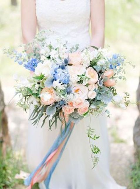 a delicate wedding bouquet of blush roses, peonies, blue delphinium, greenery and long matching ribbons is amazing