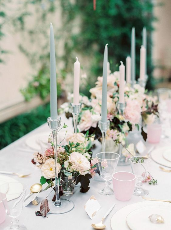 a delicate wedding tablescape with blue and blush candles, pink glasses, neutral and dark blooms and greenery plus gold cutlery